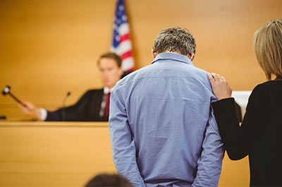 man in cuffs, lawyer, and judge in court