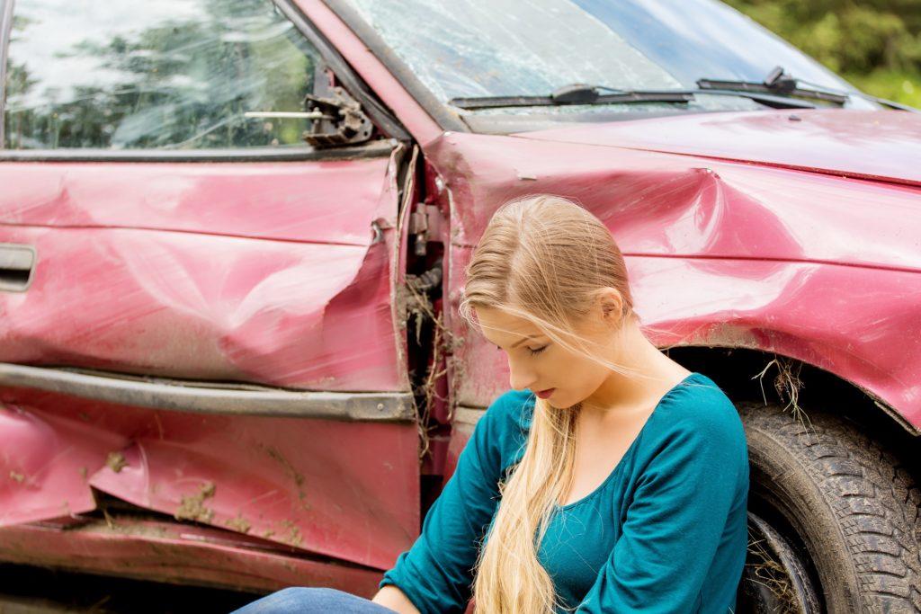 teenager sitting next to a car after being in an accident