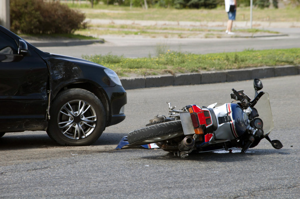 car and downed motorcycle after an accident