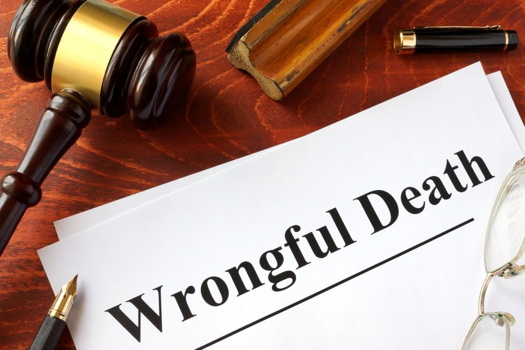 paper with wrongful death surrounded by gavel, pen, glasses- all on a wrongful death attorney's death