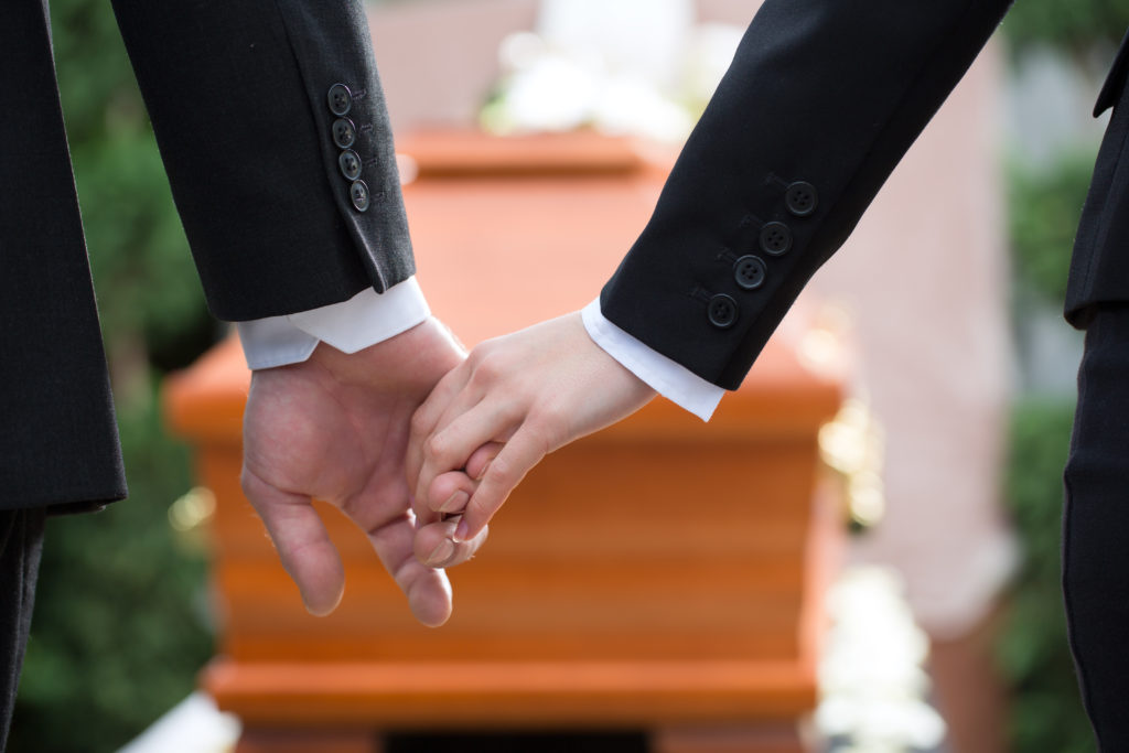 Two family members mourn at the funeral of a loved one who was the victim of a wrongful death